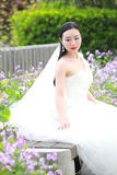 Meisjesbruid in huwelijkskleding met elegant kapsel, met de witte Zitting van de huwelijkskleding op de bank naast de omheining Royalty-vrije Stock Foto's