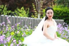 Meisjesbruid in huwelijkskleding met elegant kapsel, met de witte Zitting van de huwelijkskleding op de bank naast de omheining Royalty-vrije Stock Foto
