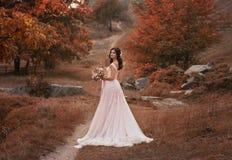 Meisjesbrunette met lang haar, in een luxueuze roze kleding met een lange trein De bruid met een boeket stelt tegen a royalty-vrije stock foto
