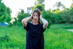 Meisjesbrunette in park in openlucht Handen die oren houden Hij schreeuwde luid Sterk luid geluid Het is onmogelijk om te luister stock afbeelding