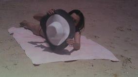 Meisjesbrunette in zwart badpak en hoed die op het strand door het overzees op de zomer zonnige dag zonnebaden stock footage