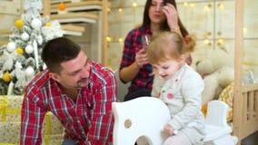 Meisjeschommeling op hobbelpaard naast haar ouders die Kerstmis vieren stock video