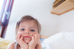 Meisjesdochter die camera bekijken aangezien zij haar ouders om van bed bij ochtend wacht te ontwaken Gelukkig ontspannen gezinsl Stock Afbeeldingen