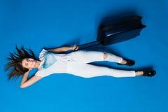 Meisjesdromen van een reis terwijl leugens op de vloer op blauwe achtergrond Vrouw met bagage die op geïsoleerde achtergrond ligg royalty-vrije stock afbeeldingen