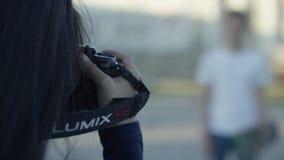 Meisjesfotograaf Fotograaf die een mooie kerel op een gang op Europese stadsstraat schieten in daglicht Het meisje neemt a stock footage