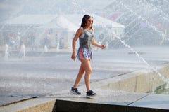 meisjesgangen onder de nevel van de fontein om aan de hitte te ontsnappen Royalty-vrije Stock Foto