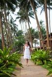 Meisjesgangen onder de palmen Meisje die op het gazon rusten bruid op wittebroodsweken Hotelgrondgebied royalty-vrije stock afbeeldingen