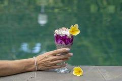 Meisjeshand die een glas met de pudding van hiazaden op de achtergrond van het zwembadwater houden De pudding van Chiazaden met r stock foto