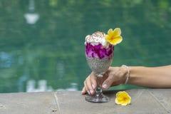 Meisjeshand die een glas met de pudding van hiazaden op de achtergrond van het zwembadwater houden De pudding van Chiazaden met r stock foto's