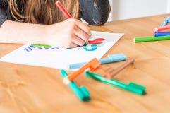Meisjeshand het schrijven de Zomervakantie in Turks die kleurrijke viltpen gebruiken terwijl het zitten bij lijst in klaslokaal royalty-vrije stock afbeelding
