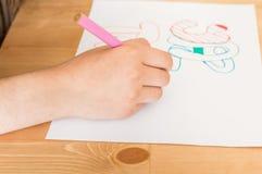 Meisjeshand het schrijven de Zomervakantie in Turks die kleurrijke viltpen gebruiken terwijl het zitten bij lijst in klaslokaal stock afbeelding