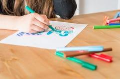 Meisjeshand het schrijven de Zomervakantie in Turks die kleurrijke viltpen gebruiken terwijl het zitten bij lijst in klaslokaal stock foto