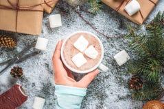 Meisjeshand met Kerstmisgiften en hete chocolade Stock Afbeelding