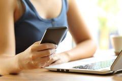 Meisjeshanden die een slimme telefoon op een bureau met behulp van Royalty-vrije Stock Afbeeldingen