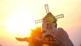 Meisjeshanden die een stuk speelgoed molen op een achtergrond van zonsondergang en zonnebloemen houden De molen roteert langzaam  stock video
