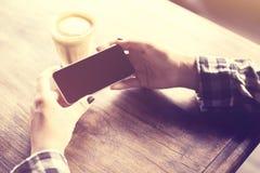 Meisjeshanden met celtelefoon en koffiemok op houten lijst Royalty-vrije Stock Afbeelding