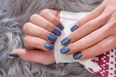 Meisjeshanden met marineblauwe nagellakkleur op de wintersweater royalty-vrije stock afbeeldingen