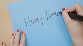 Meisjeshanden met rode spijkers die op blauw document schrijven gelukkige vaders dag met een zwarte teller - stock footage