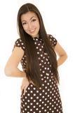 Meisjeshanden op heup die bruine stipkleding dragen Royalty-vrije Stock Foto's