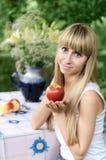 Meisjesholding Apple, zitting bij een lijst in de tuin Royalty-vrije Stock Fotografie