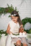 Meisjesholding in haar handen een decoratie van dienbladkerstmis Stock Foto's