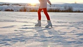 Meisjesijs die op meer tegen het plaatsen van zon schaatsen stock videobeelden