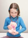 Meisjeskind die een spaarvarken houden Stock Afbeelding