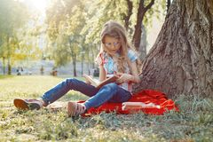Meisjeskind die in glazen boek in het park, op het gras lezen dichtbij de boom stock foto's