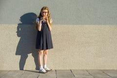 Meisjeskind die roomijs, grijze buitenmuur als achtergrond, exemplaarruimte eten stock afbeelding