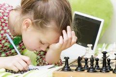 Meisjeskind het spelen schaak thuis Stock Fotografie