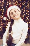 Meisjeskind het stellen met Kerstmisdecoratie op donkere achtergrond, verlichte lichten en bokeh, gezichtsclose-up, gekleed in sa Royalty-vrije Stock Fotografie