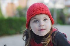 Meisjeskind in rode hoed met een vrolijke blik Stock Foto