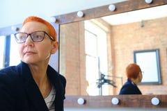 Meisjeskunstenaar in de kleedkamer Het zitten voor een spiegel met lampen Voor mooie modieuze glazen royalty-vrije stock foto