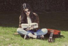 Meisjeslezing en zitting op het gras stock fotografie