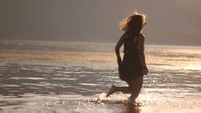 Meisjeslooppas langs de strandknieën in water stock videobeelden