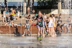 Meisjeslooppas tussen waterstralen Stock Foto