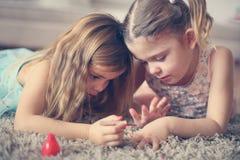 Meisjesmateriaal Meisjes op vloer Stock Fotografie