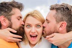 Meisjesomhelzingen met twee kerels Uiteindelijke gids die vriendenstreek vermijden De mensen kussen zelfde meisjeswangen De dame  stock afbeeldingen