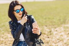 Meisjesoverseinen op telefoon en het glimlachen stock afbeelding