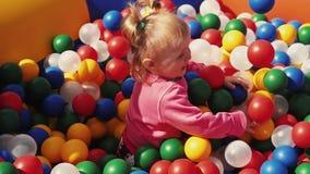 Meisjespel in kinderentrampoline met kleurenballen die wordt gevuld geluk stock video