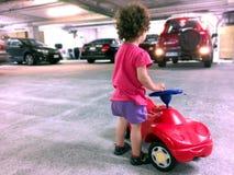 Meisjespel met een stuk speelgoed auto in parkeerterrein Stock Fotografie