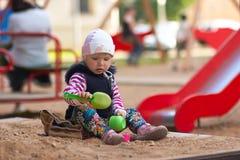 Meisjespel met speelgoed op zandbak Stock Afbeelding