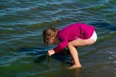 Meisjespelen in de kustgolven Royalty-vrije Stock Afbeelding
