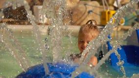 Meisjespelen met een fontein van water stock video