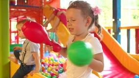 Meisjespelen met speelgoed in de speelplaats stock videobeelden