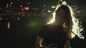 Meisjesportret in silhouet met haar die in de wind bij de achtergrond van de nachtstad golven Licht haar in de stadslichten Brand stock footage