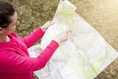 Meisjespunten op geografische kaart te plaatsen Wandeling op open gebied de jonge atleet brengt actief tijd door Het reizen op be royalty-vrije stock afbeelding