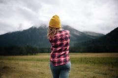 meisjesreiziger die in hoed met rugzak wolken in bergen bekijken stock afbeeldingen