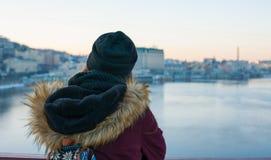 Meisjesreiziger die zich op de brug bevinden die van mening van de stad genieten Stock Foto's