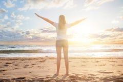 Meisjesreiziger in een dageraad van de ochtendzon op een tropisch strand resert De mooie vrouw geniet van haar de zomervakantie,  stock afbeeldingen